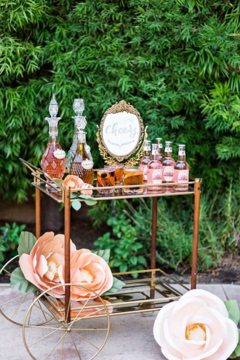 an elegant drink cart with large paper blooms and a chic gold framed sign for a backyard garden shower