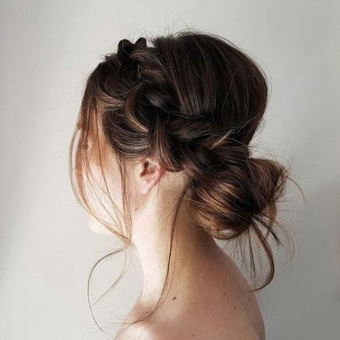 an elegant yet messy low bun with a side braid and some locks down