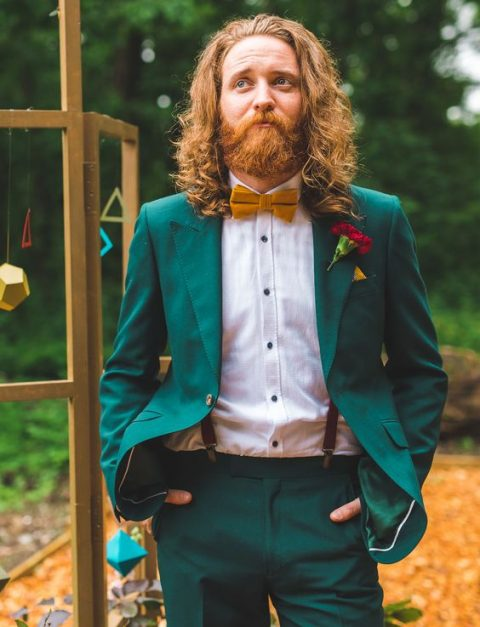 an emerald groom_s suit with a mustard bow tie and a white shirt