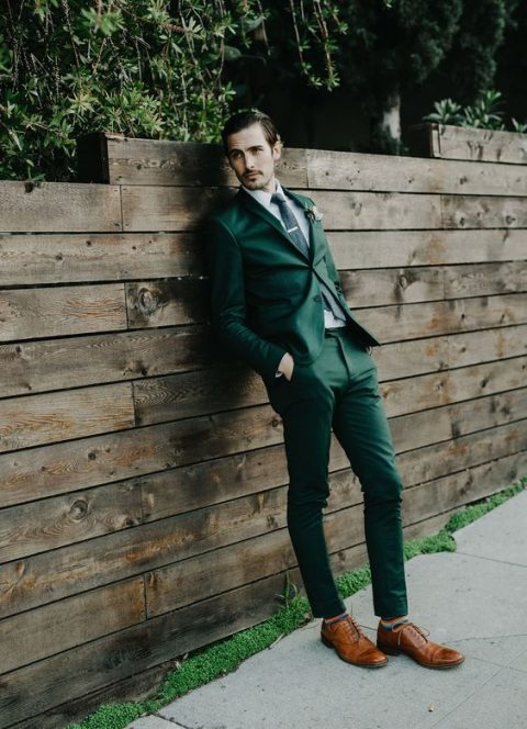 an emerald suit, a black tie and amber-colored shoes and colorful striped socks
