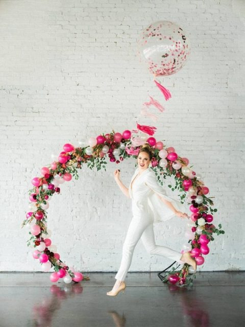 an oversized wreath balloon, greenery and floral wedding arch in hot pink and blush for a modern glam wedding