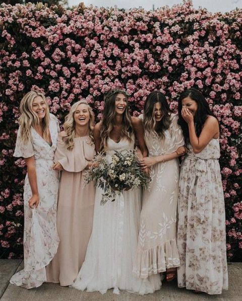 bridesmaids in mismatched floral maxi dresses and in blush ones