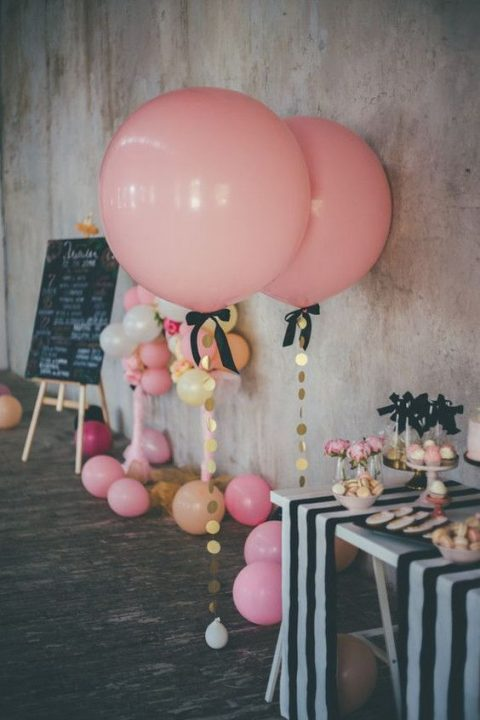 oversized pink balloons with gold sequins and black bows for decorating a dessert table