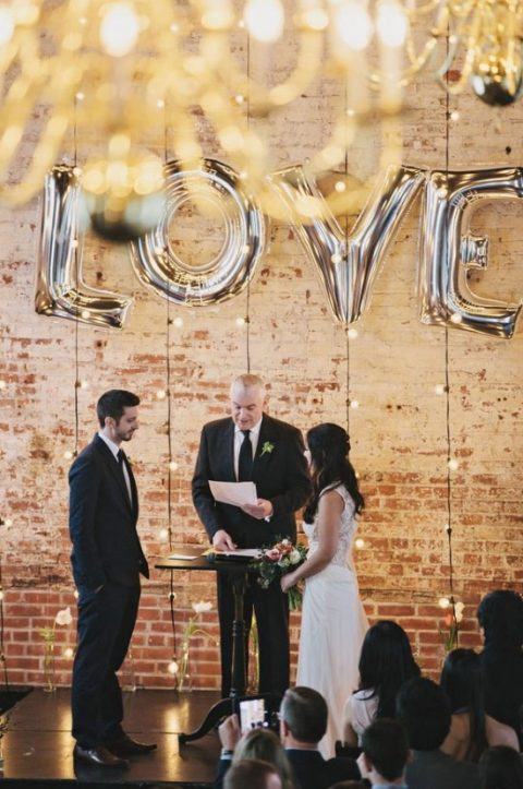 string lights and oversized LOVE balloons for a modern wedding ceremony