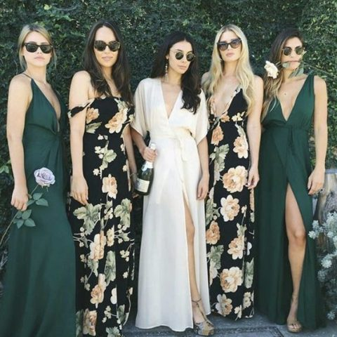 two bridesmaids in dark floral maxi gowns and two in dark green ones