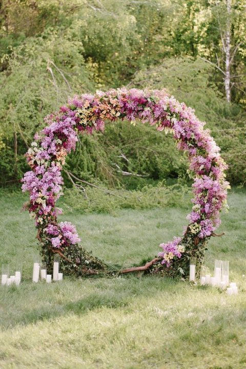 a beautiful circular floral wedding arch in the shades of pink and lilac plus candles around