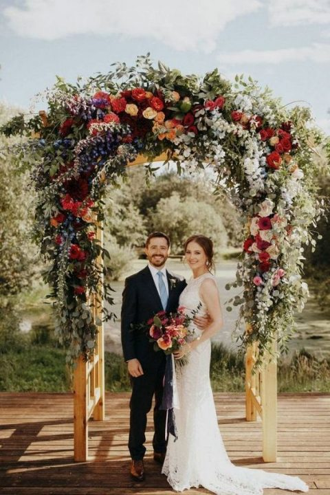 a beautiful floral wedding arch done in lots of colors and lush greenery for a bright wedding