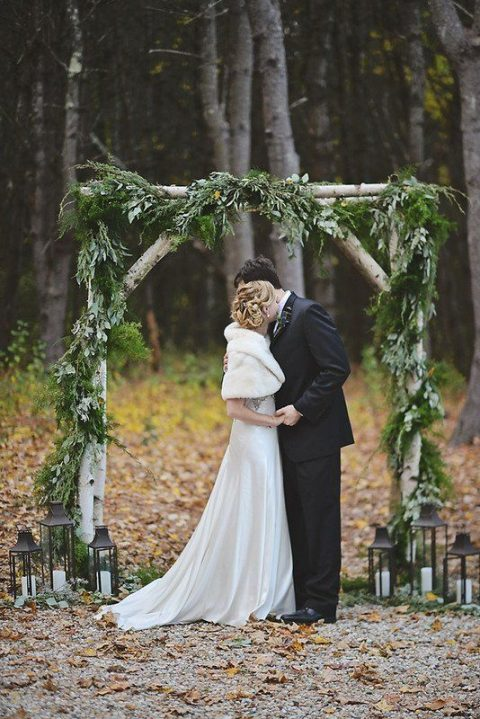 a birch branch wedding arch decorated with ferns, fir and greenery, candle lanterns