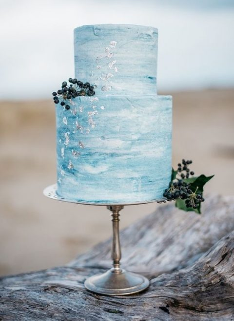 a blue watercolor wedding cake decorated with silver leaf and some berries for a coastal wedding