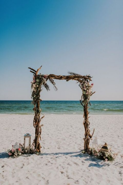 a boho driftwood wedding arch with blush blooms and some herbs plus candle lanterns around