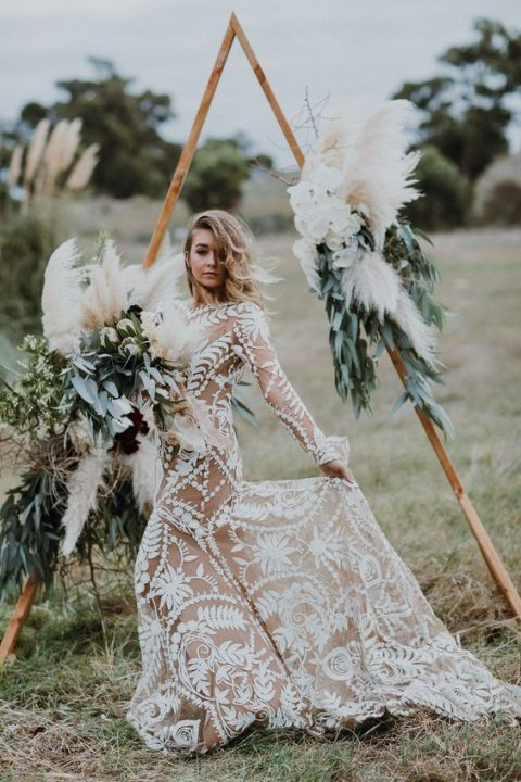 a boho triangle wedding arch with foliage, herbs and pampas grass, which is a hot trend