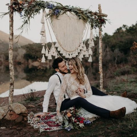 a boho wedding backdrop with branches, lush greenery, wildflowers and a macrame hanging