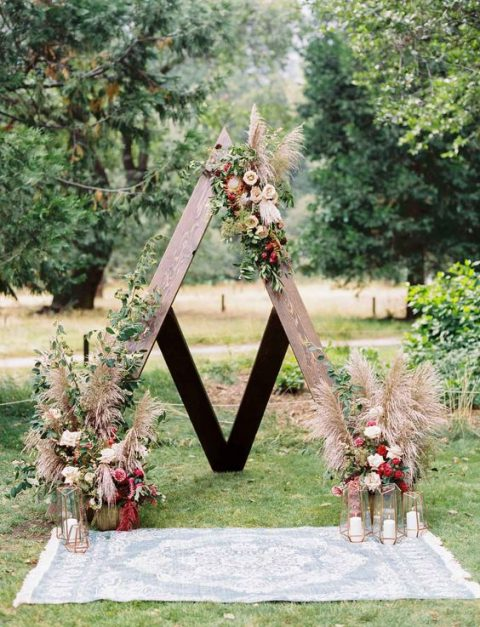 a boho wooden arch decorated with greenery, fall-colored blooms and pampas grass plus candles in geometric candle holders