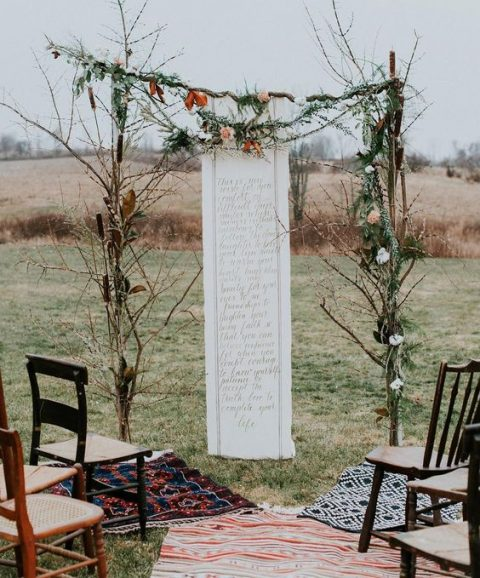 a branch wedding arch with leaves and a quote backdrop
