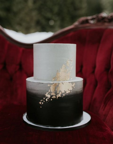 a brushed ombre black and white wedding cake with gold leaf decor