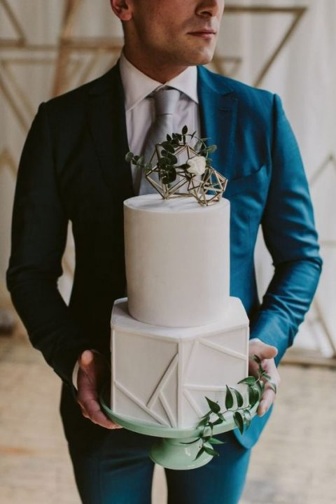 a buttercream wedding cake with textural geometric decor, a gold geometric topper with greenery on top