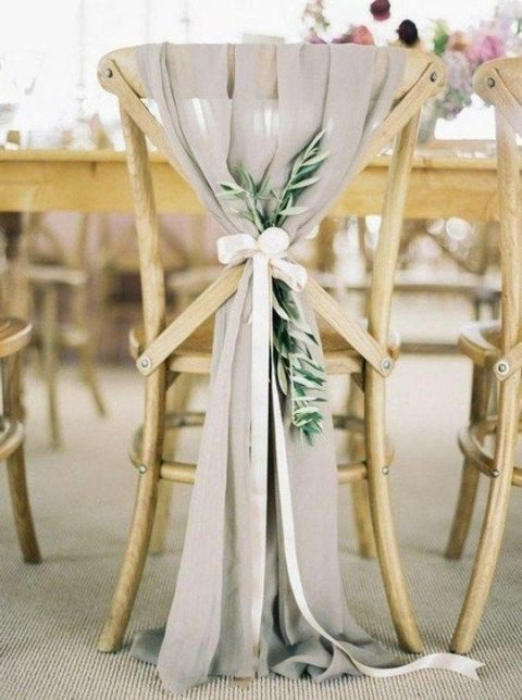 a chair decor with airy grey fabric, eucalyptus and a ribbon bow