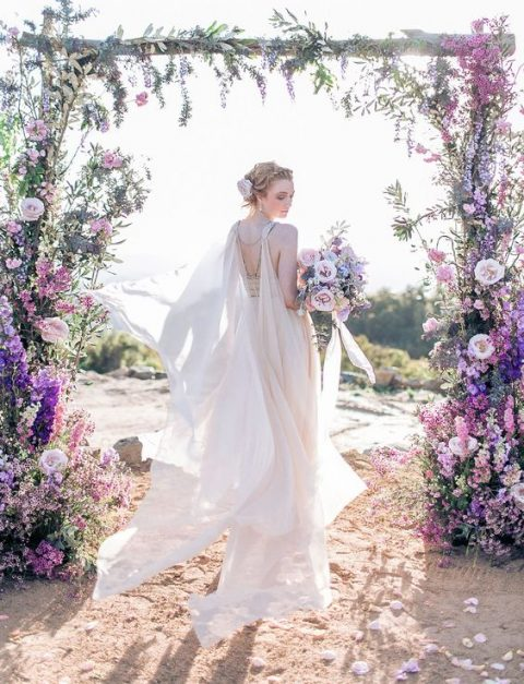 a chic wedding floral arch in the shades of purple and lilac looks very natural as if flowers are growing themselves like that