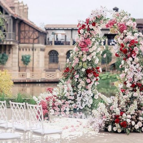 a colorful wedding arch with burgundy, pink and white blooms and much texture