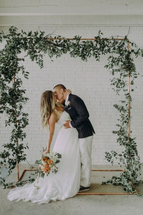 a copper wedding arch decorated with lush greenery is a elegant minimal idea
