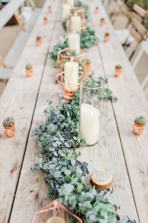a cute greenery and foliage table runner with candles and copper canlde holders