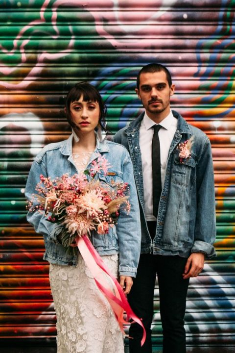 a distressed denim jacket instead of a usual blazer plus a pink floral boutonniere for a fun touch
