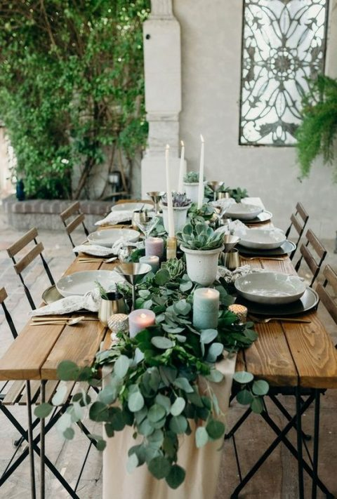 a eucalyptus table runner with succulents in pots, with pastel candles and tall white ones