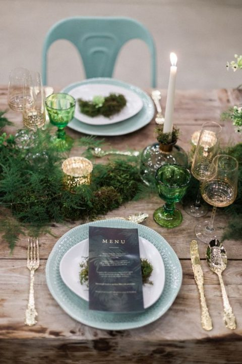 a fern table runner, tall candles and green glasses and mercury glass candle holders on an uncovered table