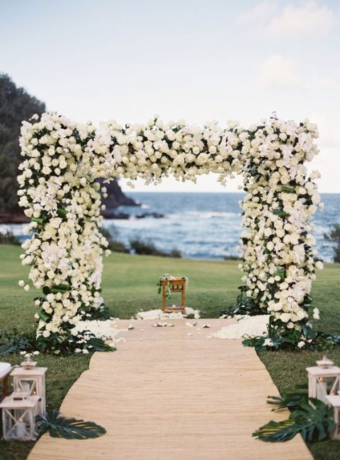 a floral arbor fully covered with white roses and a backdrop of the ocean for a romantic feel