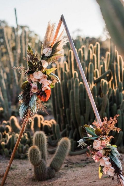 a gorgeous metal triangle wedding arch decorated with leaves, pampas grass and lush large blooms for a bold look