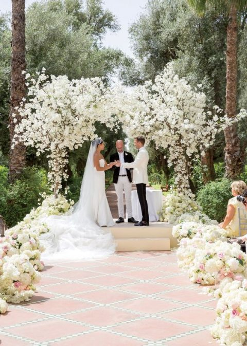 a gorgeous wedding arch done with white blooms and branches arranged as blooming trees and lush aisle lining