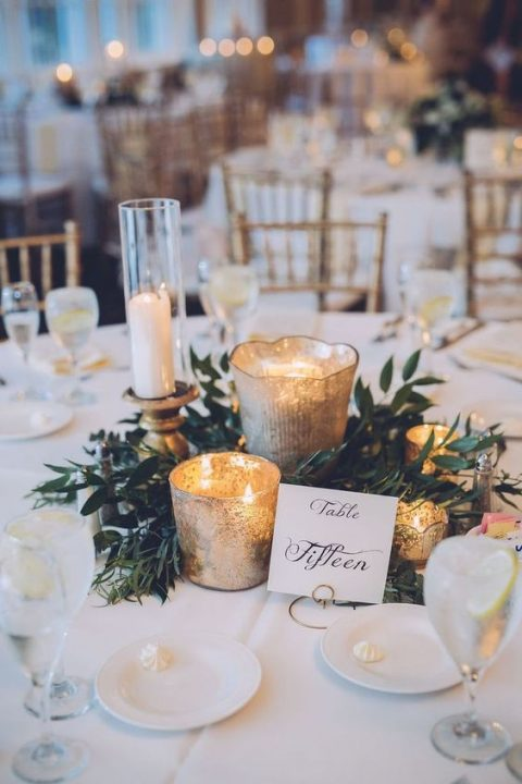 a greenery and mercury glass candle holder centerpiece with a calligraphy table number