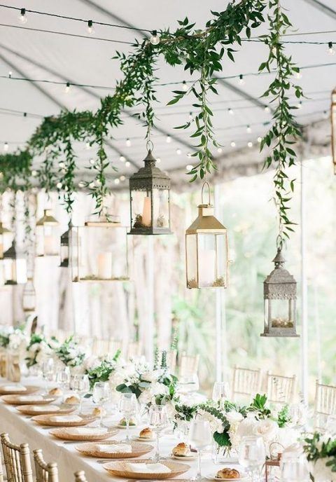 a greenery garland with lanterns hanging on them as a reception decoration