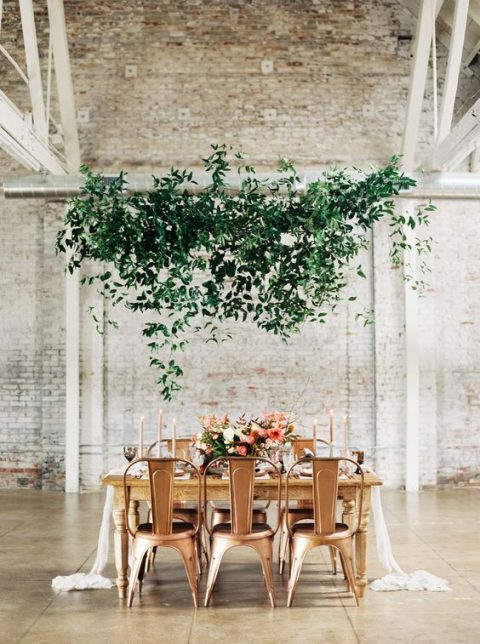 a greenery installation over the reception space for a fresh feel