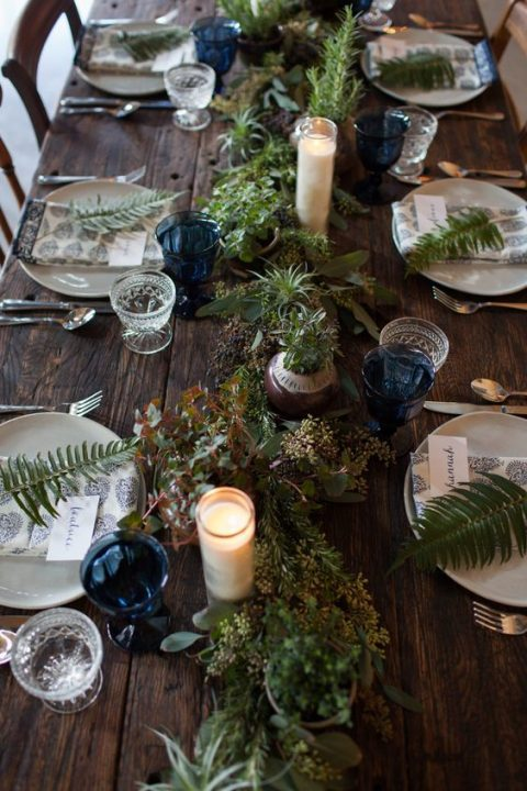 a greenery table runner with various types of it, succulents and air plants plus candles