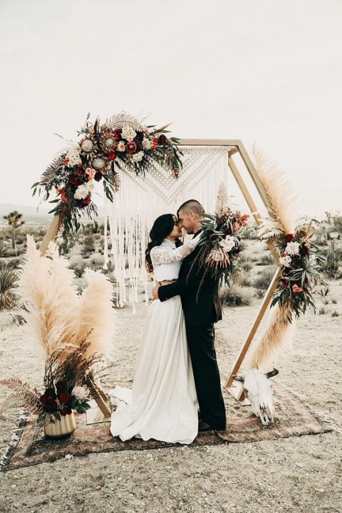 a hexagon wedding arch with a macrame hanging, pampas grass, lush florals and greenery plus a boho rug