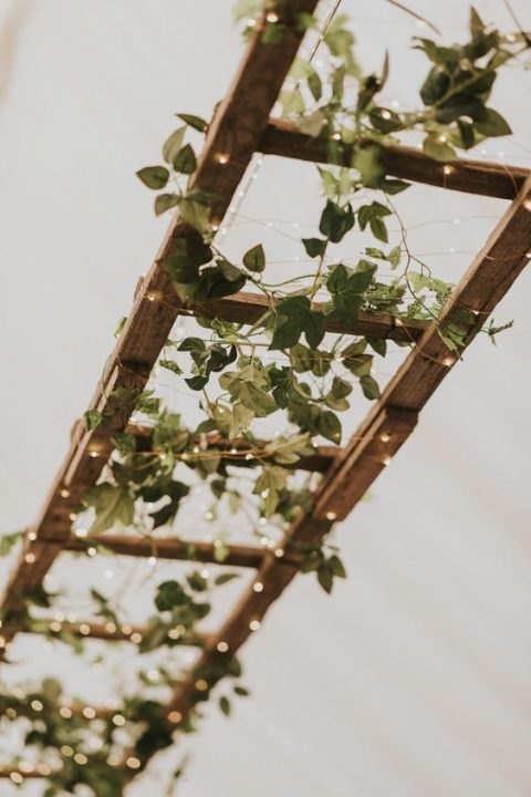 a ladder with greenery and LEDs over the reception table is a cute decoration idea