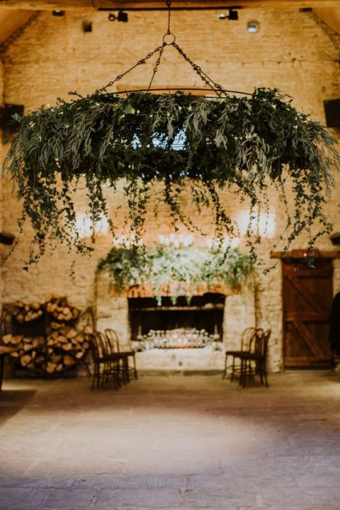 a large cascading greenery chandelier with LEDs for a barn wedding