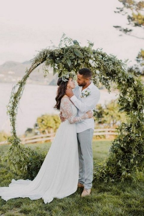 a large circular wedding arch covered with textural greenery