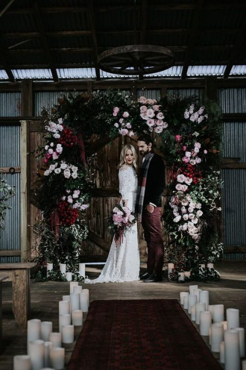 a lush and moody wedding arch with greenery, burgundy and pink blooms and ferns for a Halloween wedding