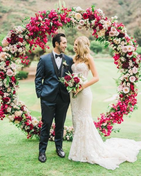 a lush circular wedding arch with fuchsia, red, pink and burgundy blooms