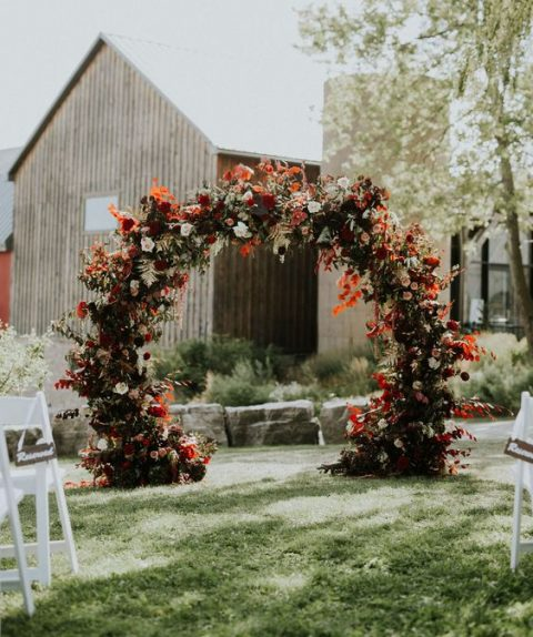 a lush dark autumn wedding arch with red leaves and blooms, white roses and much greenery