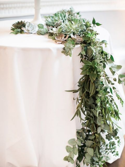 a lush eucalyptus and succulent table runner features much texture and various shades