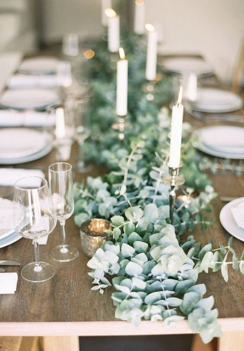 a lush eucalyptus table runner with mercury glass candle holders and metallic holders