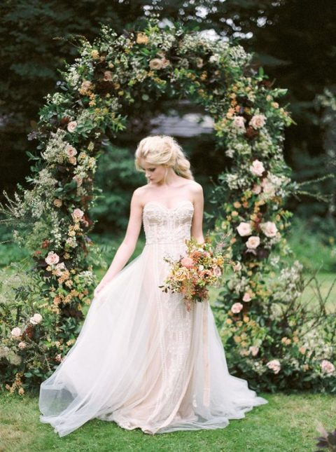 a lush fall hygge wedding arch with greenery, blush, yellow and deep purple blooms