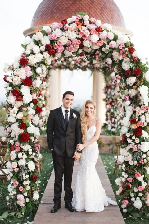 a lush floral wedding arch done in white, pink and deep red looks amazing