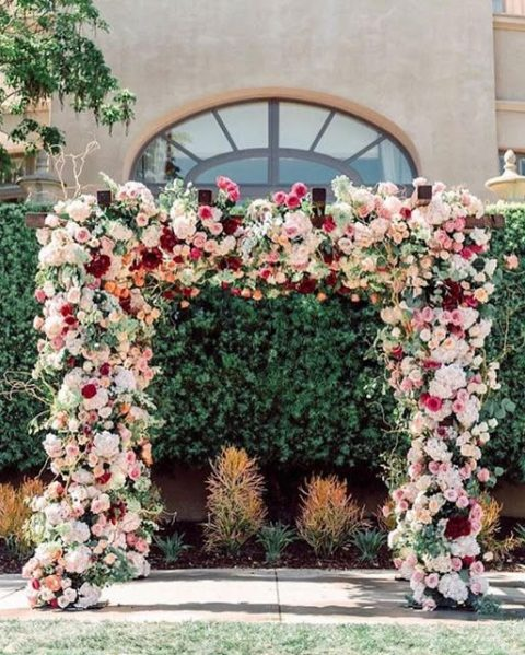 a lush floral wedding arch with creamy, pink and burgundy blooms i ideal for summer or fall