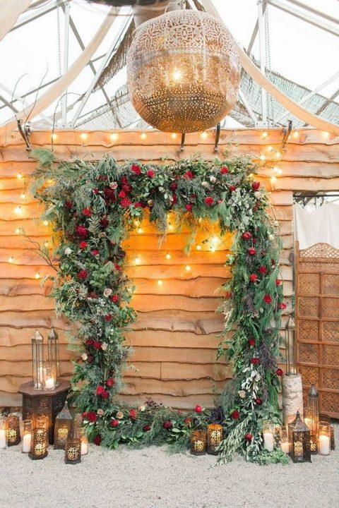 a lush frame Christmas wedding arch of greenery and red and burgundy roses plus candles and candle lanterns around