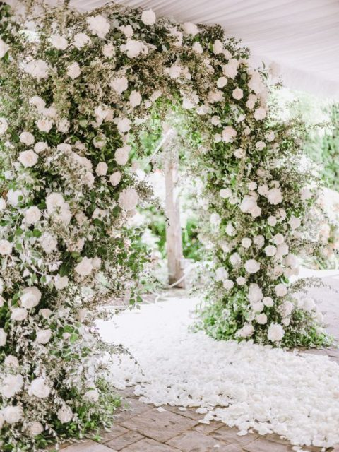 a lush greenery and white bloom wedding arch and lots of white flower petals