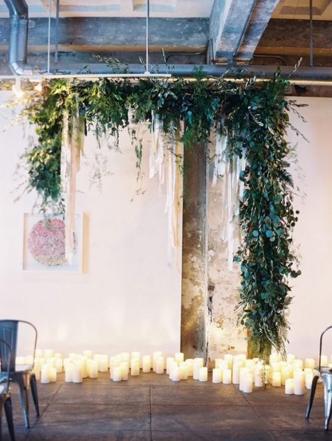a lush greenery arch with cascading elements plus pillar candles down